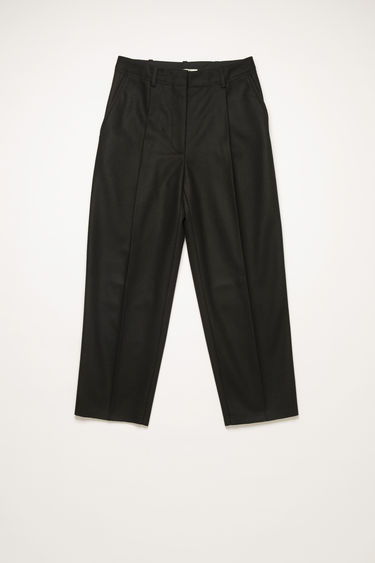 Acne Studios black trousers are cut to sit high on the waist and shaped to a tapered-leg fit with front pleats.