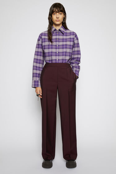 Acne Studios aubergine/black trousers are tailored in a straight-leg shape with an elasticated waistband and has a faux front placket and neatly pressed creases.