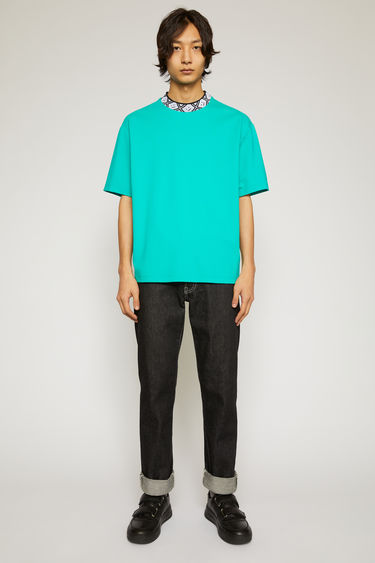 Acne Studios jade green t-shirt is cut to a relaxed silhouette from midweight stretch jersey and features a ribbed mock neck inlaid with a face-jacquard design.