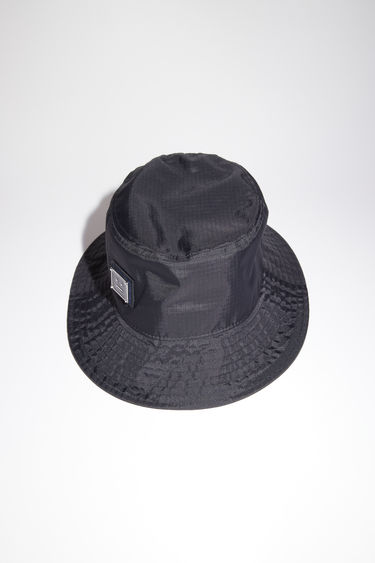 Acne Studios black bucket hat is made from technical ripstop and features a polished metal logo plaque with a face motif in black.