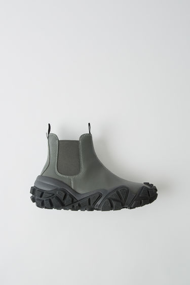 Acne Studios green/black ankle boots are set on exaggerated rubber soles with trekking-inspired lugs. They are crafted from smooth calf leather and have elastic side panels.