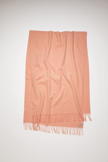 Acne Studios salmon pink oversized fringed scarf is made of pure wool, featuring a label in one corner.