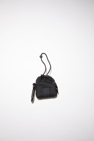 Acne Studios black drawstring earbud case is made from technical ripstop with a face logo patch. It has a drawstring closure and dogclip.