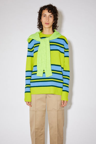 Acne Studios green/blue striped crew neck sweater is made from wool with a face logo patch and ribbed details.