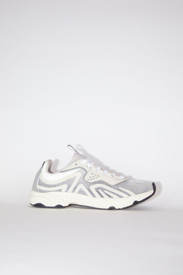 Acne Studios white/ivory sneakers feature a combination of running and trail elements in one silhouette. They're crafted from semi-transparent ripstop with faux suede overlays and set on a cushioned sole.