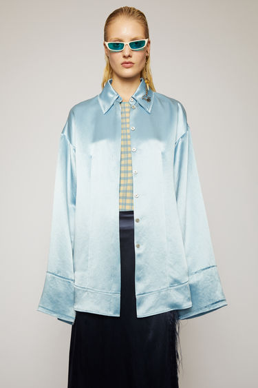Acne Studios powder blue satin shirt is crafted to an oversized fit with dropped shoulder seams and purposefully finished with raw, frayed edges along the collar, cuffs and hem.
