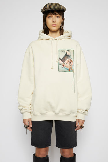 Acne Studios warm white hooded sweatshirt is crafted from organic cotton to a relaxed silhouette with dropped shoulders and adorned with a printed patch, featuring a prize dog created by Britsh artist Lydia Blakeley.