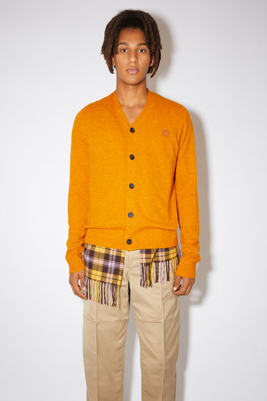 Acne Studios carrot orange v-neck cardigan sweater is made from wool with a face logo patch and ribbed details.