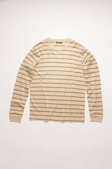 Acne Studios cream beige long-sleeved t-shirt is cut from lightweight cotton jersey that's patterned with double stripes and accented with a tonal face-embroidered patch on the chest.