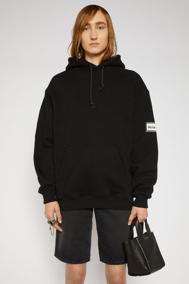 Acne Studios black hooded sweatshirt is crafted from organically grown cotton to a relaxed silhouette with dropped shoulders and adorned with a reversed label patch on the sleeve.