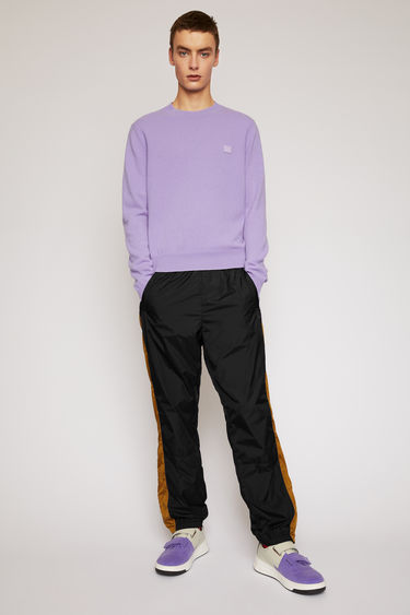 Acne Studios black track pants are made from shell and has an elasticated waistband and hem. They are accented with a face-embroidered patch and stripes down the sides.