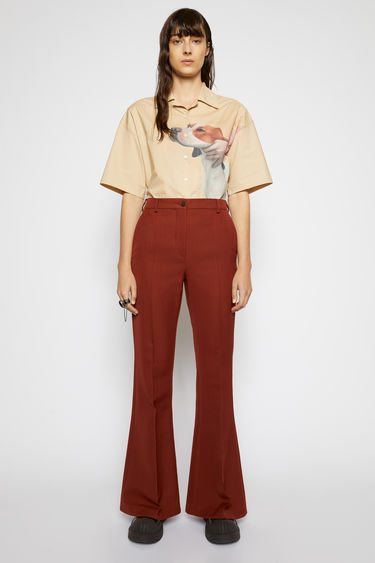 Acne Studios rust brown trousers are cut to sit high on the waist that gradually flare out on the lower leg and is neatly finished with pressed creases down the front and back.
