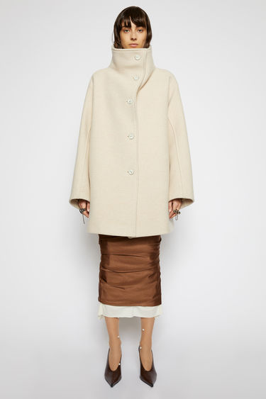 Acne Studios cream beige coat is crafted from boiled wool to an oversized, A-line silhouette with a wide funnel neckline and sleeves and adorned with tonal ceramic buttons.