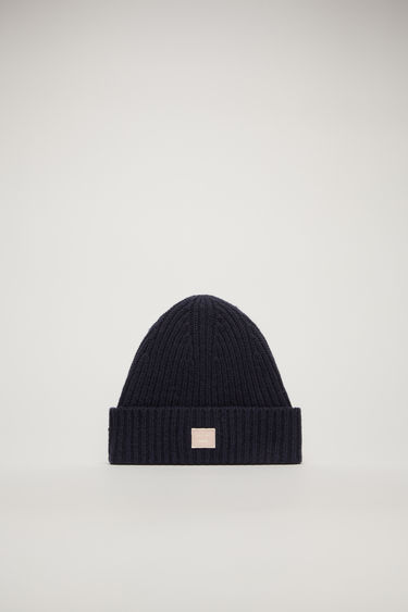 Acne Studios Mini Pansy N Face navy/pink beanie is rib-knitted from soft wool and detailed with a face-embroidered patch on the turn-up brim.
