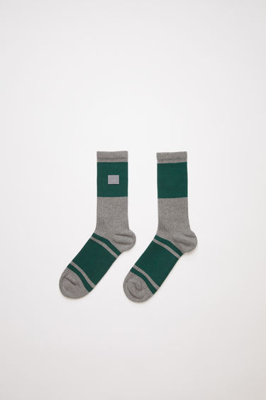 Acne Studios grey melange/forest green striped socks are knitted from a cotton blend in a thick rib-stitch and feature a jacquard face motif design and a soft, towelling footbed.