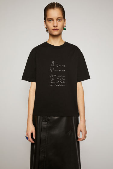 Acne Studios black t-shirt is cut to a boxy silhouette from cotton jersey and features a handwritten logo and headquarter's address embroidered on the front.
