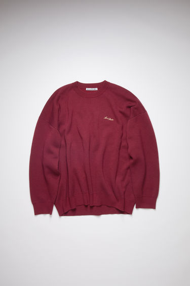 Acne Studios cherry red crew neck sweater is a double face knitwear in wool and cotton with an embroidered logo at the chest.