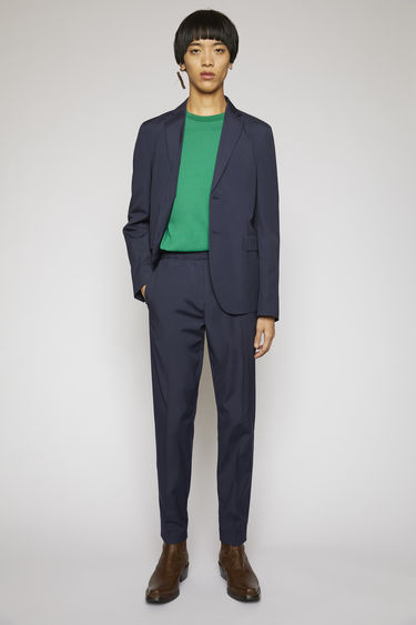 Acne Studios dark blue trousers are made from cotton with a sheen finish and shaped with slim legs with a mid-rise elasticated waistband.
