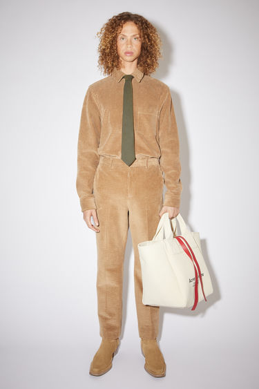 Acne Studios camel brown tailored trousers are made of a cotton corduroy with a slight stretch.