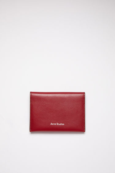 Acne Studios burgundy multi colour block bifold card holder is made of soft grained leather with four card slots and a silver stamped logo on the front.