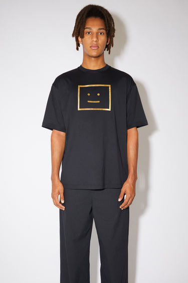 Acne Studios black crew neck t-shirt is made from organic cotton with a relaxed fit and a metallic face logo print.