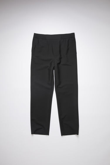 Acne Studios black wool blend trousers are shaped with straight legs with a cropped length and finished with an elasticated waistband with a flat front panel.