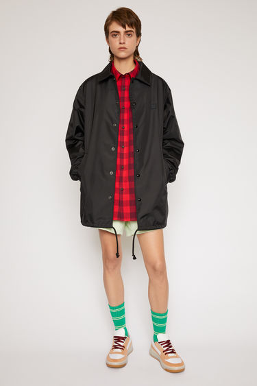 Acne Studios black coach jacket is shaped with a point collar and a drawstring waist and features a face motif print across the back.