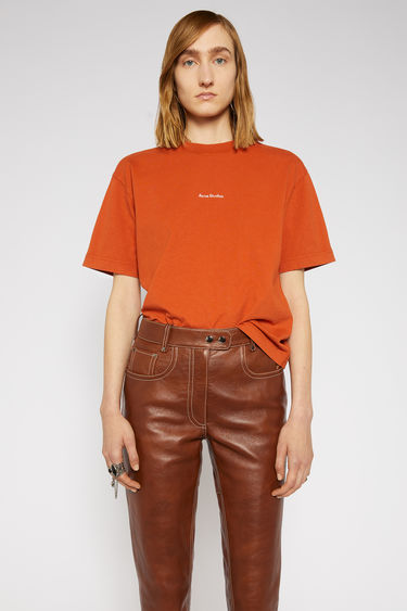 Acne Studios pumpkin orange t-shirt is made from pigment-dyed jersey that's lightly faded along the seams. It's cut to a relaxed silhouette with dropped shoulders and features a raised logo print on front.