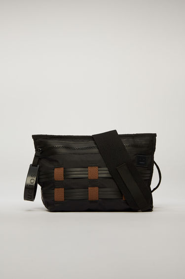 Acne Studios black/brown belt bag is crafted from ripstop and detailed with flat rubber cords woven on the front. It is equipped with a front zip pocket, mesh pocket, and an adjustable buckled strap.