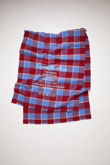Acne Studios cherry red/sky blue oversized, checked scarf is made of wool with a large, printed care label.