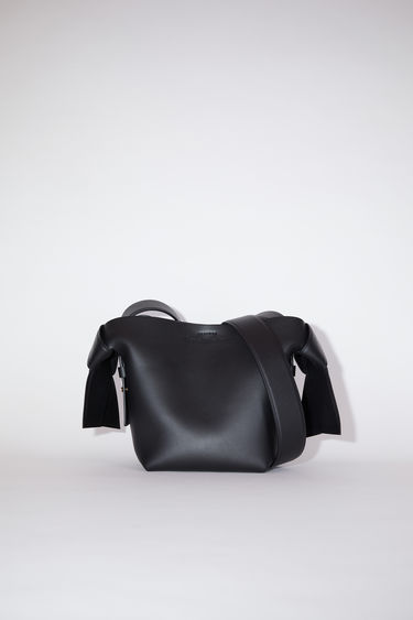 Acne Studios black small bag features twisted knots inspired by traditional Japanese obi sashes. It has a debossed logo and snap button closure, which opens to reveal a zipper compartment for storing small essentials.