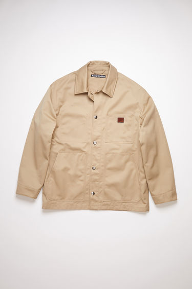 Acne Studios beige unlined workwear jacket is made of crisp cotton twill with a face logo patch.