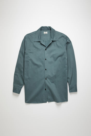 Acne Studios dusty green shirt is made from cotton twill that's been garment dyed for softness. it's crafted to a boxy silhouette that falls loosely across the frame with a point collar and button-down front.