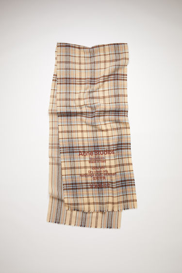 Acne Studios oat beige/brown narrow, tartan check scarf is made of wool with a large, printed care label.