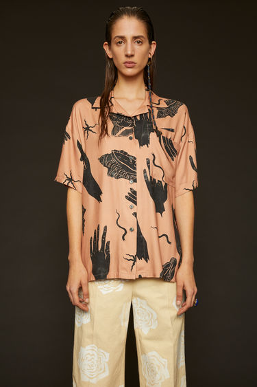 Acne Studios pink/black shirt is shaped to a relaxed fit with dropped shoulder seams and wide, short sleeves and illustrated with hand and shell motifs.