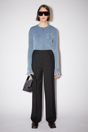 Acne Studios black trousers are cut to a straight-leg fit with a mid-rise elasticated waist and feature a faux front placket and pressed creases.