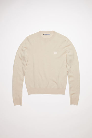 Acne Studios cream beige crew neck sweater is made from wool with a face logo patch and ribbed details.