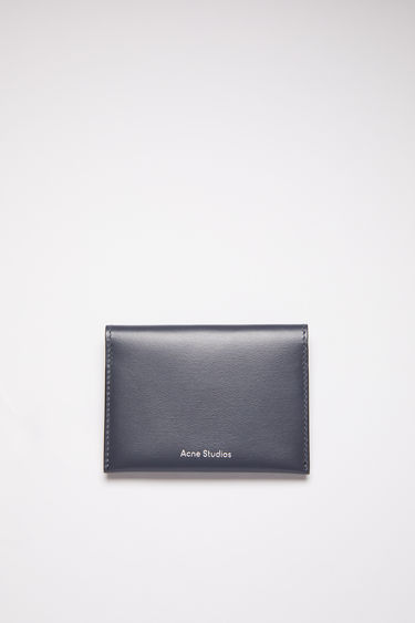 Acne Studios dark blue bifold card holder is made of soft grained leather with four card slots and a silver stamped logo on the front.