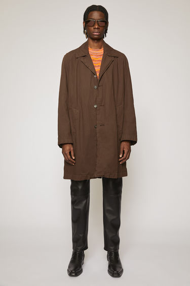 Acne Studios coffee brown trench coat is crafted from washed cotton to an A-line silhouette and finished with two side slip pockets and tonal buttons down the front.