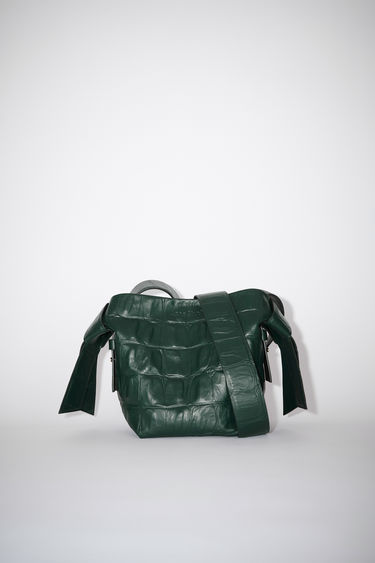 Acne Studios emerald green small bag features twisted knots inspired by traditional Japanese obi sashes. It has a debossed logo and snap button closure, which opens to reveal a zipper compartment for storing small essentials.