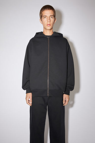 Acne Studios black oversized hooded sweatshirt is made of a cotton blend, featuring an Acne Studios logo tab on the lower side.
