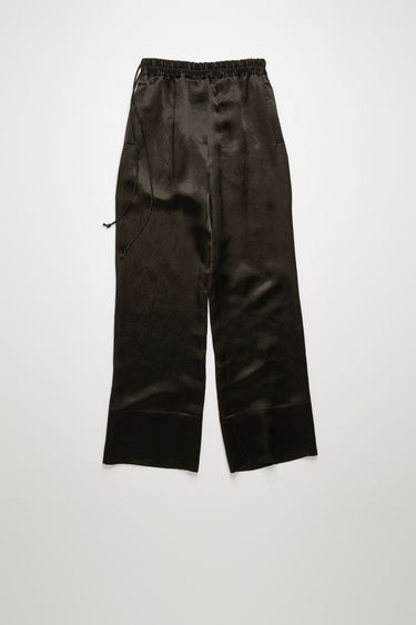 Acne Studios black satin trousers are cut to a relaxed fit with straight legs and feature an elasticated waist with drawstrings at side.