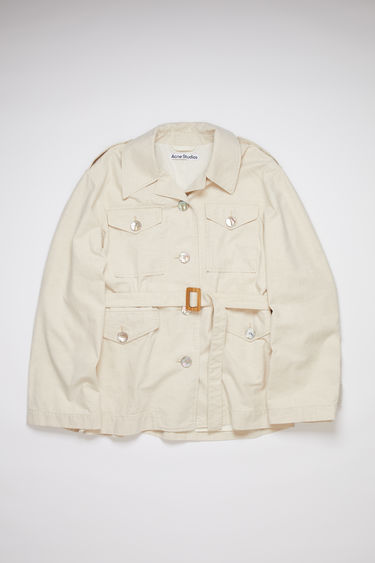 Acne Studios cream beige belted coat is made of cotton with a relaxed fit.