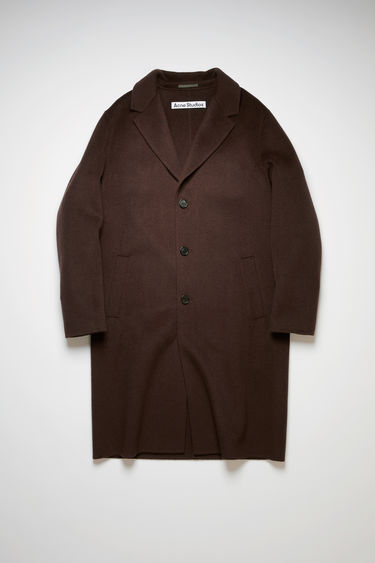 Acne Studios cacao brown coat is crafted from double-faced wool to an oversized cocoon silhouette and features wide notched lapels, side welt pockets and three button closures.