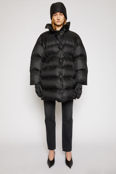 Acne Studios black puffer coat is crafted from recycled down and feather-filled shell and is shaped to an oversized silhouette with softly rounded shoulders. The funnel collar has a packaway hood and is finished with an adjustable belt for a personalised fit.