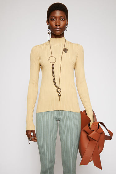 Acne Studios sand beige mock neck sweater is knitted from a mercerized cotton in an irregular rib pattern and shaped to a figure-skimming fit.