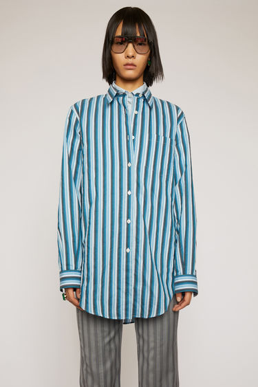 Acne Studios bright blue striped shirt is crafted from cotton to a relaxed fit and features a chest patch pocket, point collar and a shirttail hem.