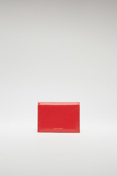 Acne Studios red bifold cardholder is crafted from high-shine leather and features four card slots and a gold stamped logo on the front.