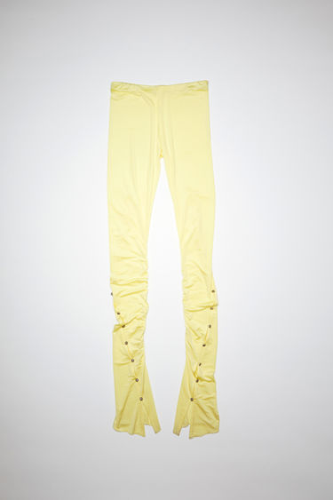Acne Studios lemon yellow elastic waist trousers have shirred, flared legs and ornate metal buttons.