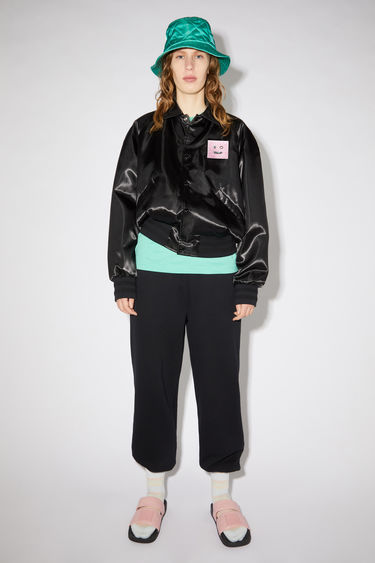 Acne Studios black varsity-inspired jacket is made of shiny satin and features a large face patch at the chest.